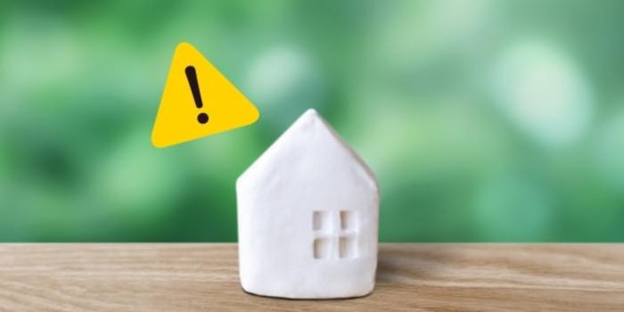 家の模型と注意マーク